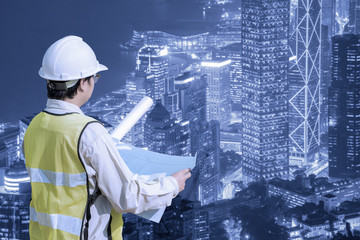 Construction engineer checking construction drawing with modern cityscape view for new Infrastructure construction project concept