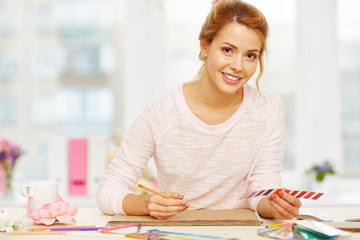Smiling attractive designer working in modern office with color swatches, messy desk covered with pencils, notebook and other stationery