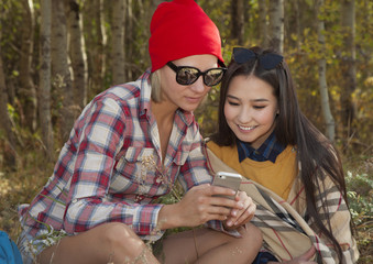Two young woman tourist with mobile phone