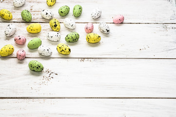 Easter background with colorful easter eggs on white wooden boards