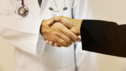 Doctor shaking a patient's hands; concept vintage tone.