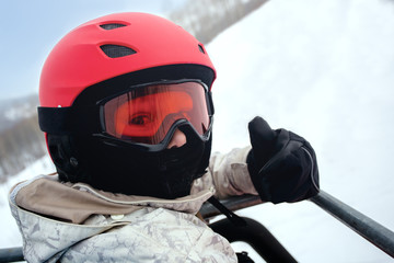 Girl skier in a red helmet and goggles