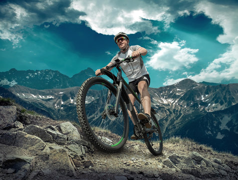 Man in helmet and glasses stay on the bicycle under sky with clo