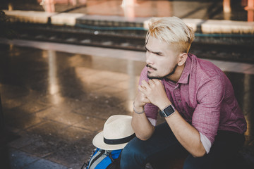 Young hipster man sitting on wooden bench with backpack at train station. man sitting waiting for the train at platform.