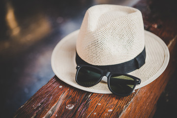 Hat and sunglasses on wooden bench at train station. Travel concept.