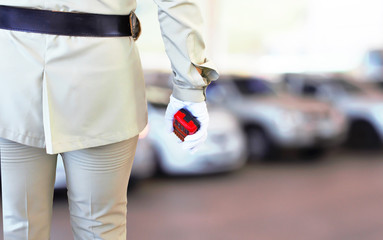 Close of of policewomen's hand on his transmitter. Security agent surveillance guard in park car blur background concept.