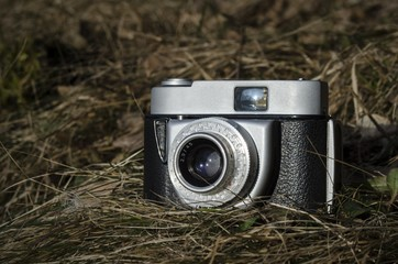 Old vintage analog photo camera in nature grass background