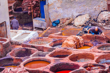 Stacks of leathers in Fez, Morocco, while man is washing them