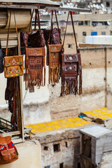 Leather bags being sold, over old buildings background