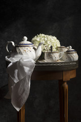 A tea service set on a table, on a dark background