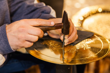 Craftsman hands with hammer working on a golden plate