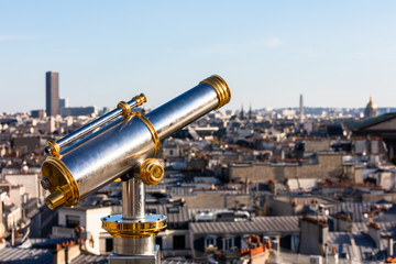 Touristic telescope overlooking Paris from the roof of department store