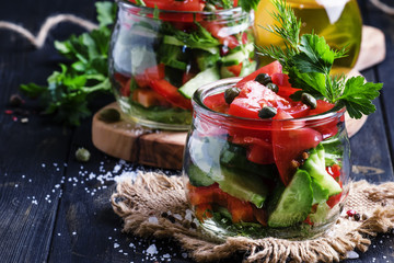 Vegan salad with vegetables, herbs, capers and olive oil in glass jars, selective focus