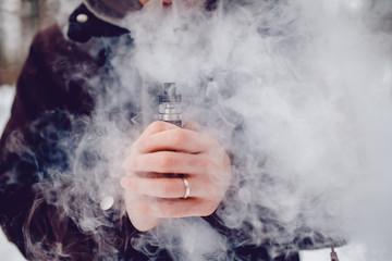 vaping man holding a mod device. cloud of vapor. Vape