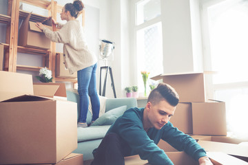 Couple moving in new home and unpacking boxes