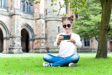 Young teenage girl taking picture in Glasgow University garden.