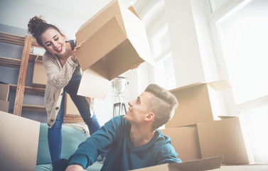 Couple moving in new home and having fun during unpacking boxes