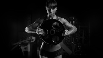Black and white photo of fit power athletic confident young woman bodybuilder doing exercises with heavy weight barbell plate in gym