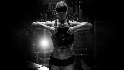 Black and white portrait of fit power athletic confident young woman crossfit trainer doing...