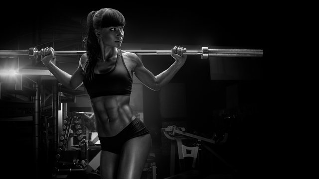 Black and white photo of fit young woman in great shape lifting barbells looking focused, working out in a gym