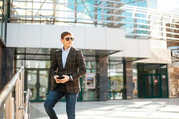 A handsome young businessman in sunglasses standing and waiting for something