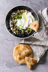 labneh middle eastern lebanese cream cheese dip with olive oil, salt, herbs, olives tapenade served in black bowl with traditional pita bread over gray texture metal background. Top view with space
