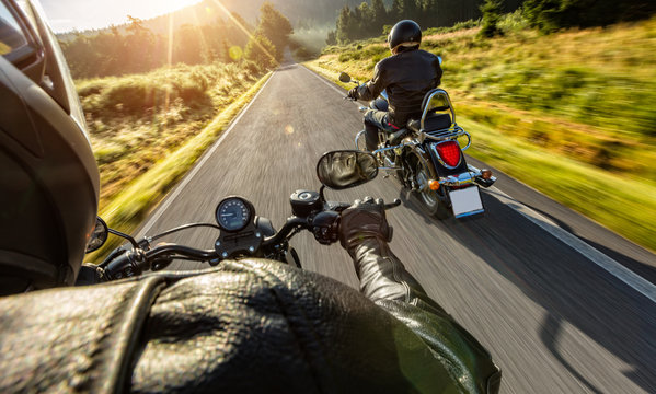 Two motorbikers riding on empty road