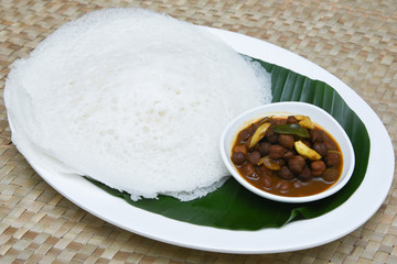 Appam / Palappam / Kallappam / vella appam / plain hoppers, popular traditional Kerala breakfast dish with hot spicy egg roast curry on houseboat, Alleppey, India. South Indian food. Sri lankan