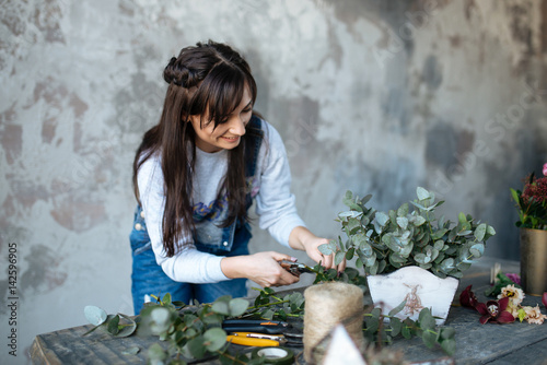 Female In Gray Blouse And Jeans Make A Bouquet Over Gray Background