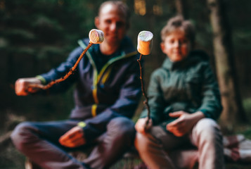 Father and son prepear to bake marshmallow candies on campfire