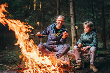 Father and son roast marshmallow candies on campfire