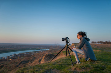 A tripod with a camera shoots the landscape