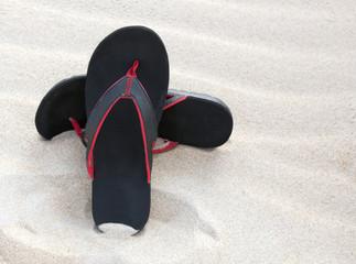 Black flip-flop sandals in beach sand.