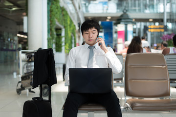 Asian businessman using smartphone and laptop while waiting for his flight in terminal at airport.