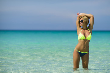 Beautiful young blond woman in yellow swimsuit is standing in the azure water of caribbean sea