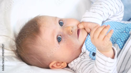 baby mit gro en blauen augen und blonden haaren im bett stockmaterial und lizenzfreie videos. Black Bedroom Furniture Sets. Home Design Ideas