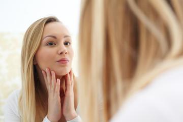 Fototapeta Pielęgnacja skóry. Kobieta przegląda się w lustrze  i sprawdza stan skóry obraz