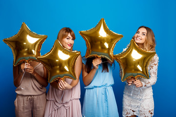 Four beautiful girls resting at party over blue background.