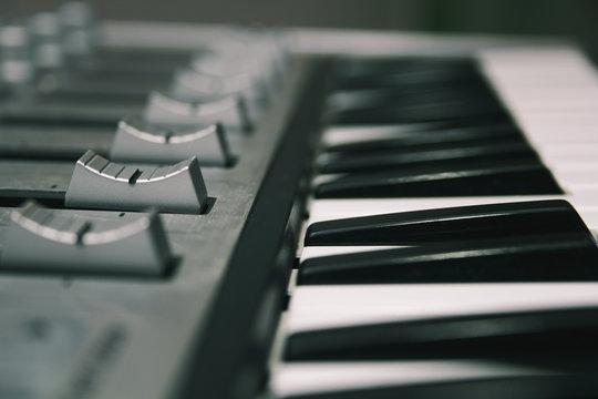 Midi keyboard close-up, keys and faders