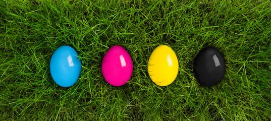 Fototapete - cmyk easter eggs lying in grass