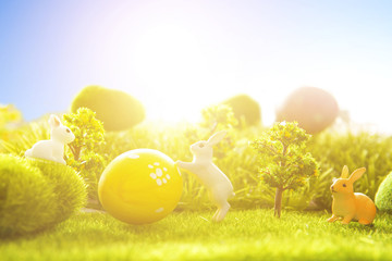 Rabbits with easter eggs on green meadow over sundown. Cute Little easter bunny on spring flowers and green grass. Sunbeams. Happy Easter