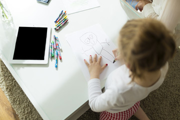 Child drawing with crayons at home.