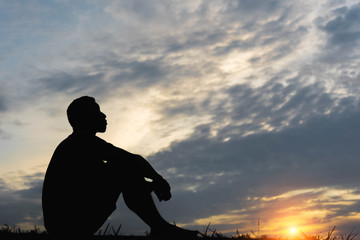 Silhouette of a man sitdown with so sad in the sunset. Wall mural
