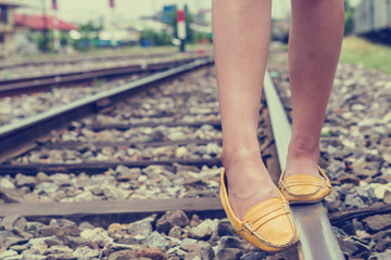 Asian young girl walking along railway station, walking on the train track
