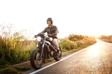 Young handsome man riding on motorbike at countryside road. Flare sunlight background.
