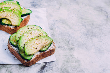 Healthy toast with cottage cheese, green cucumber and avocado on wooden board on a marble gray table background. Horizontal image, top view top, copy space. Vegetarian food content
