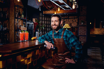 Portrait of a barman hipster with  beard smiling sitting in  bar.