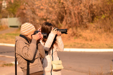 Two women photographers take photos together in the fall. Side view