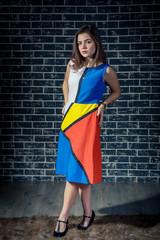 Studio portrait of beautiful teen brunette girl wearing colorful dress