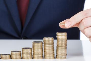 Businessman hand stacking one euro coins into increasing columns. Financial concept. Closeup.